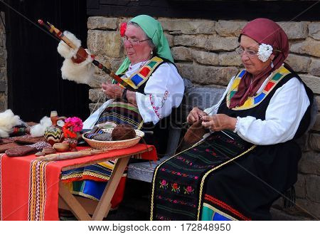 ETAR GABROBO PROVINCE BULGARIA - JUNE 19 2016: Two aged Bulgarian women spin and knit outside the house