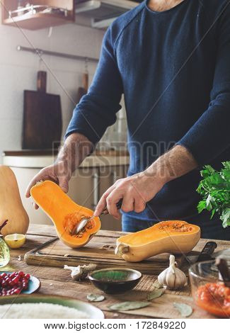 Man preparing healthy food of a squash on a wooden table in a home kitchen. Delicious and healthy homemade food