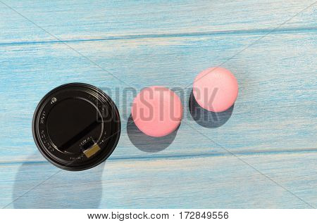 Hot drink and two pink macaroons on blue wooden table