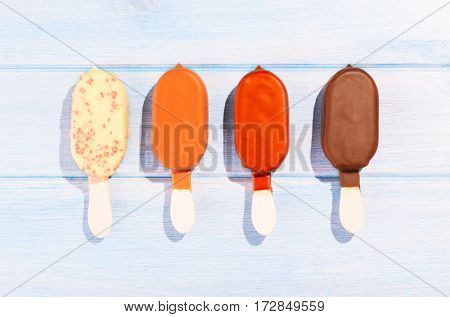 Four different ice creams on blue table outdoors