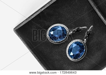Pair of large sapphire earrings in black jewel box closeup