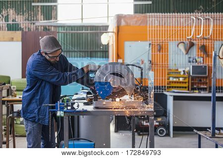 Side view of professional man working on saw machine making sparkles