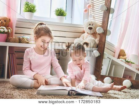 Two cute little children are reading a book. Happy girls play at home. Funny lovely sisters are having fun in children room.
