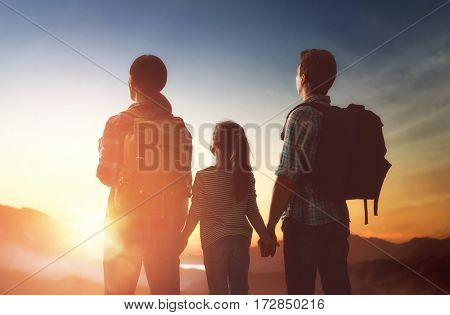Happy family at sunset. Father, mother and child daughter having fun and enjoying journey.