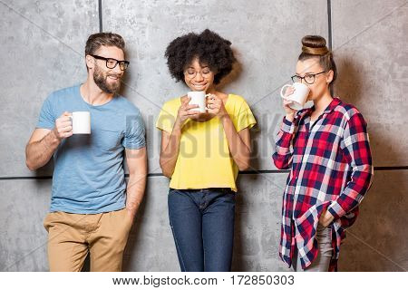 Multi ethnic coworkers dressed casually having a coffee break near the gray wall indoors