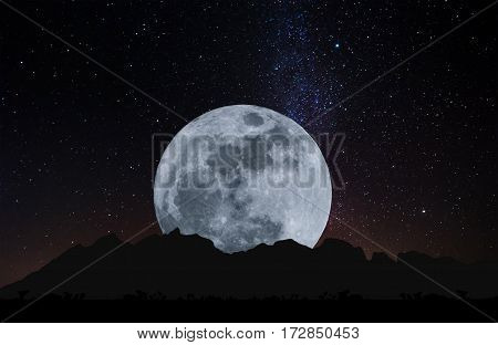 Silhouette mountain ridge with Full moon at night and the sky full of colorful stars