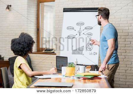 Multi ethnic coworkers dressed casually in colorful clothes working during the meeting at the office with laptop, documents and whiteboard