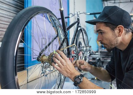 Bearded man checking measurments of bicycle at workshop