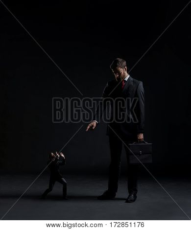 Boss punishing worker over black background. Businessman and subordinate.