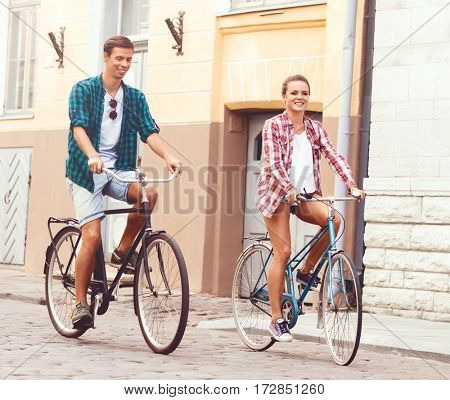 Young couple of hipsters riding a bicycle. Date in old town. Love, relationship, romance concept.