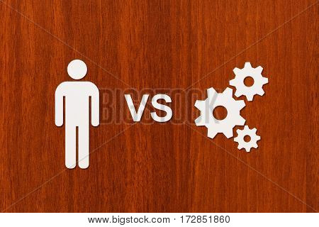Paper man vs technology cogwheels mechanism. Wooden background. Abstract conceptual image