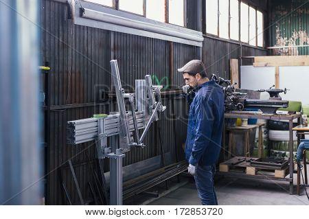 Craftsman working with metal details at workshop