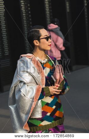 MILAN ITALY - FEBRUARY 22: Fashionable woman poses outside Gucci fashion show building during Milan Women's Fashion Week on FEBRUARY 22 2017 in Milan.