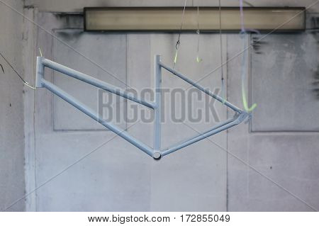 Grey bicycle frame hanging against of wall in garage