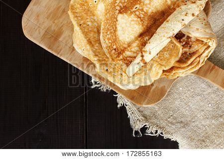 flat layout of a pile of pancakes on a dark wooden table top view / lush appetizing evening meal