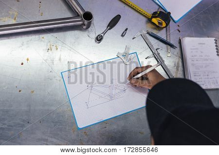Professional craftsman doing drawing with pen of bicycle