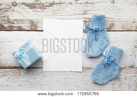 beautiful gift, baby's socks and blank postcard on white wooden background