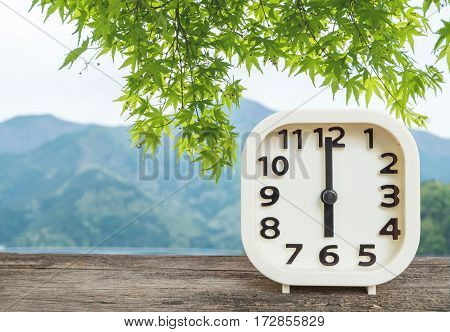 Closeup white clock for decorate in 6 o'clock on blurred mountain view background