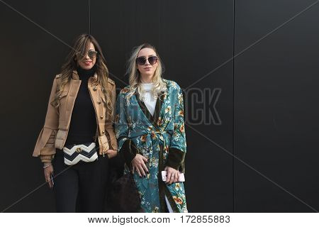 MILAN ITALY - FEBRUARY 22: Fashionable women pose outside Gucci fashion show building during Milan Women's Fashion Week on FEBRUARY 22 2017 in Milan.