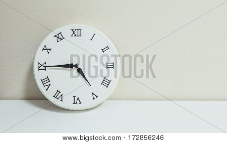 Closeup white clock for decorate show a quarter to five p.m. or 4:45 p.m. on white wood desk and cream wallpaper textured background with copy space