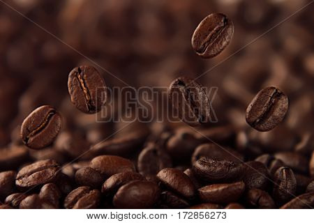 Falling coffee bean on background of heap of roasted beans.