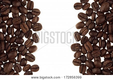 Heap roasted coffee beans as decorative frame with copy space isolated on white background.