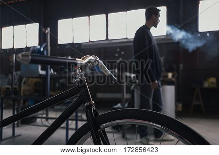 Close-up of new constructed bicycle and smoking craftsman on background