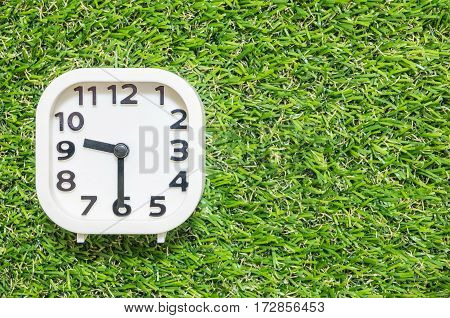 Closeup white clock for decorate show a half past nine or 9:30 a.m. on green artificial grass floor textured background with copy space