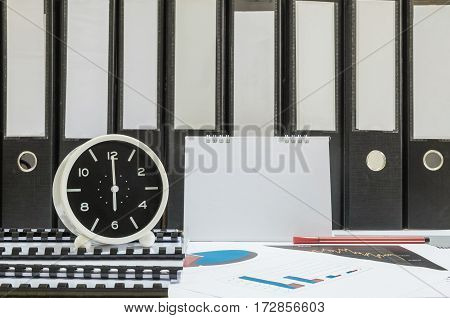 Closeup white clock for decorate in 6 o'clock desk of officer with work paper and document file in office room textured background in work concept