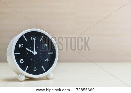 Closeup alarm clock for decorate in 10 o'clock on brown wood desk and wall textured background with copy space