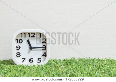 Closeup white clock for decorate show a quarter past eleven or 11:15 a.m. on green artificial grass floor and cream wallpaper textured background with copy space
