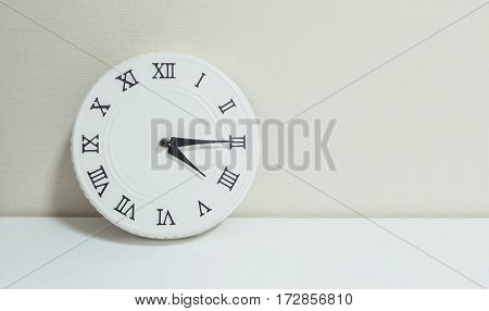 Closeup white clock for decorate show a quarter past four or 4:15 p.m. on white wood desk and cream wallpaper textured background with copy space