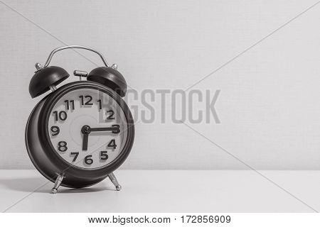 Closeup alarm clock for decorate show a quarter past six or 6:15 a.m.on white wood desk and cream wallpaper textured background in black and white tone with copy space