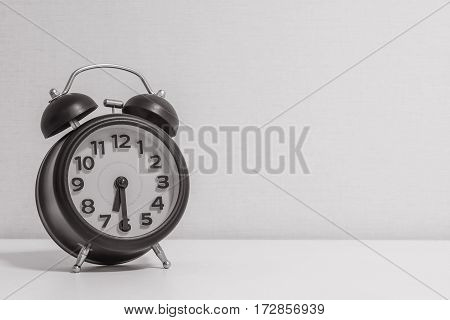 Closeup alarm clock for decorate show half past six or 6:30 a.m.on white wood desk and cream wallpaper textured background in black and white tone with copy space