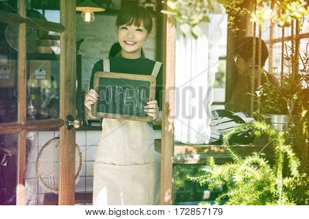 Young woman holding banner open the cafe