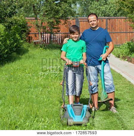 Father and son mowing the lawn and trimming the edges together in summer time