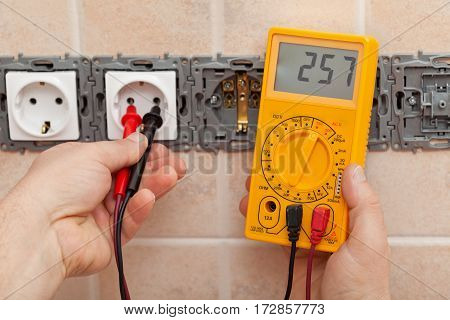 Electrician checking voltage in a partially installed electrical wall socket with electronic multimeter