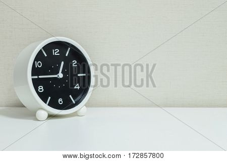 Closeup black and white alarm clock for decorate in a quarter to one or 12:45 p.m. on white wood desk and cream wallpaper textured background with copy space