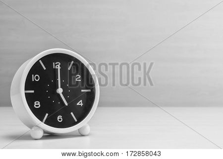 Closeup alarm clock for decorate in 5 o'clock on wood desk and wall textured background in black and white tone with copy space