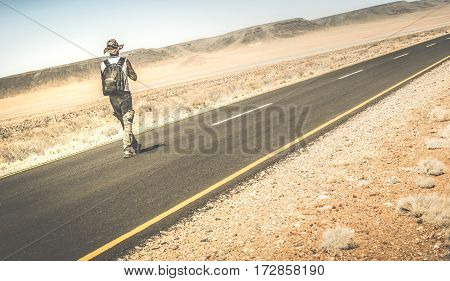 Man walking on the road on namibian african desert - Alternative lifestyle concept and wanderlust experience with guy backpacking to unknown - Travel trip adventure around the world - Retro filter