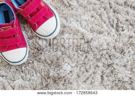 Closeup red fabric sneakers of kid on gray carpet textured background in top view with copy space