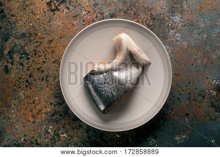 Whole piece of smoked salmon on the plate. Dark background