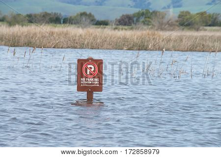 Parking lot sign submerged in flood waters after recent torrential rain fall. Flooded.