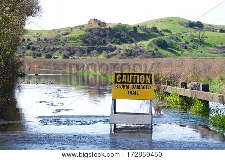 Caution storm damaged trail sign up in front of flooded pedestrian trail along Coyote Canyon northern california