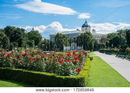 A view of Volksgarten park with flowering red roses in front of Hofburg Vienna Austria.