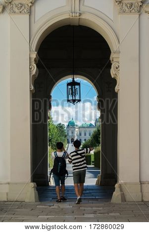 VIENNA AUSTRIA - JULY 29 2016: Two tourists making photo at the entrance of Belevedere palace in Vienna Austria on sunny summer day.