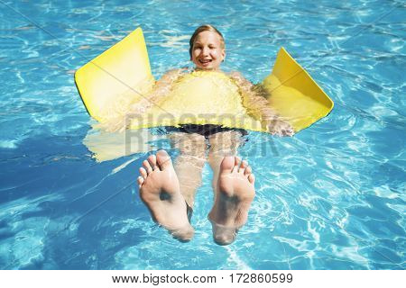 Teenager swims on a mat in the pool