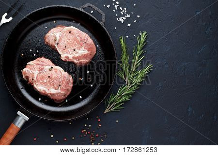 Raw Pork Chops On Pan With Rosemary, Salt And Pepper On Stone Background.