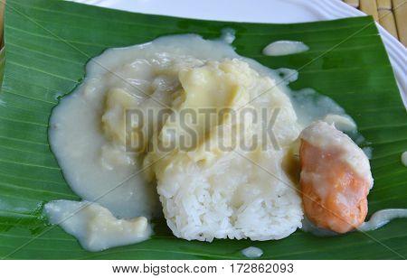 durian sticky rice dressing coconut cream on banana leaf
