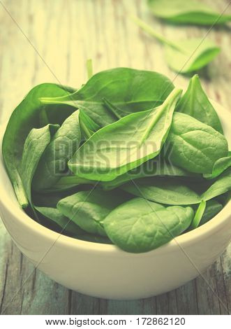 Fresh Baby spinach leaves in white bowl on blue wooden background. Top view with copy space, vertical, toned. Healthy, Ecology concept